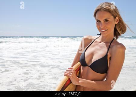 Frau am Strand mit einem Surfbrett stehend - Stockfoto