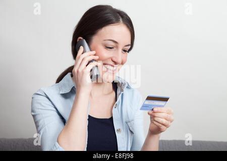 Frau am Telefon mit Kreditkarte - Stockfoto