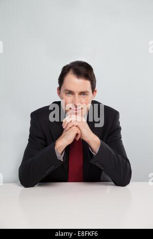 Porträt des Kaufmanns am Tisch sitzen - Stockfoto