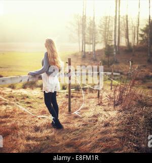Frau am Zaun in ländlicher Landschaft mit Blick auf die Aussicht, Norwegen - Stockfoto