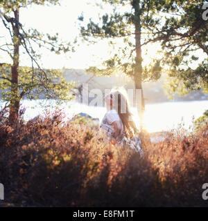 Frau, die an einem See steht und den Kopf zurückwirft, Norwegen - Stockfoto