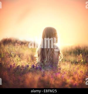 Frau auf einer Wiese bei Sonnenuntergang über ihre Schulter schauend, Norwegen - Stockfoto