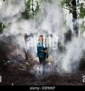 Frau, die in einem nebligen Wald steht und eine Kamera hält, Norwegen - Stockfoto