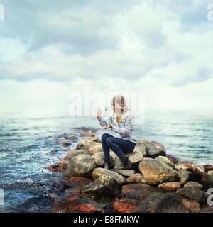 Frau sitzt auf Felsen am Meer und löst einen Schmetterling aus einem Glas, Norwegen - Stockfoto