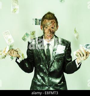 Blutiger Mann in einem schmutzigen Anzug, der Geld in die Luft wirft - Stockfoto