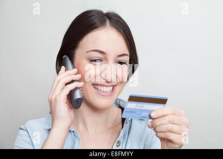 Nahaufnahme von Frau am Telefon mit einer Kreditkarte - Stockfoto