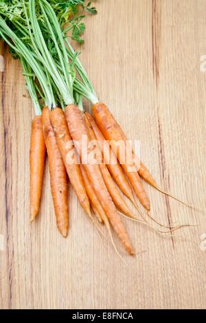 Rohe Karotten auf einem Holztisch - Stockfoto