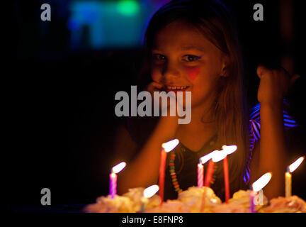 Lächelndes Mädchen mit Herz Form Gesicht malen sitzen ihre Geburtstagstorte - Stockfoto