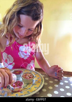 Mädchen, die Muffins dekorieren - Stockfoto