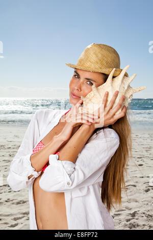 Junge Frau hört Muschelmuschel am Strand, Kapstadt, Westkap, Südafrika - Stockfoto