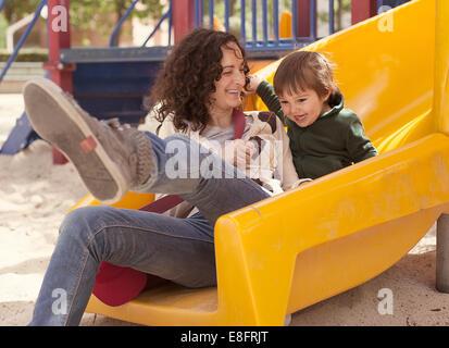 Mutter und Sohn auf einer Folie auf Spielplatz - Stockfoto