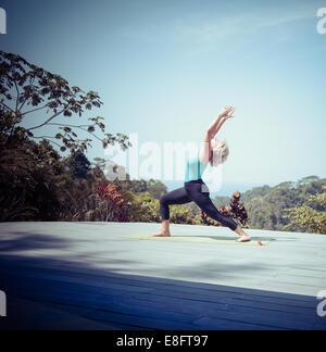 Frau, die eine hohe Longe Yoga machen stellen im Freien, Costa Rica - Stockfoto