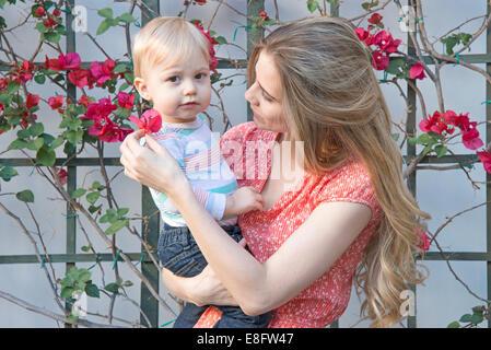 Mutter und Kind (12-17 Monate) hält Blume im Garten