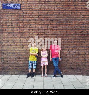 Drei Kinder stehen vor der Ziegelmauer - Stockfoto
