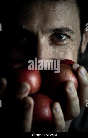 Italien, Lombardei, Mailand, Mann hält Äpfel mit seinen Händen - Stockfoto