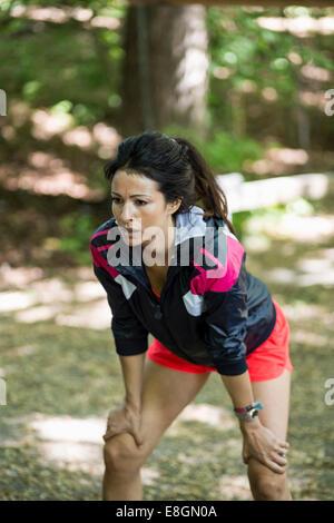 Müde Frau stehend mit den Händen auf den Knien beim Outdoor-Fitness-Studio - Stockfoto