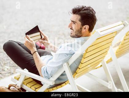 Glücklich Kaufmann wegsehen bei der Verwendung von digital-Tablette auf Liege am park - Stockfoto