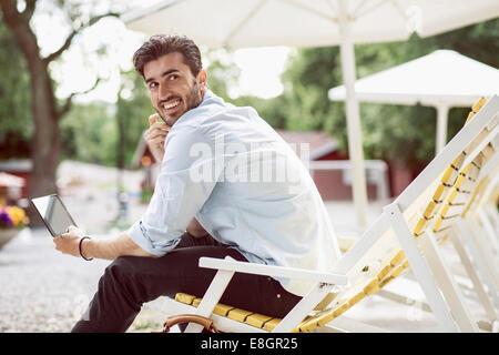 Seitenansicht des glücklichen Geschäftsmann wegsehen bei der Verwendung von digital-Tablette auf Liege am park - Stockfoto