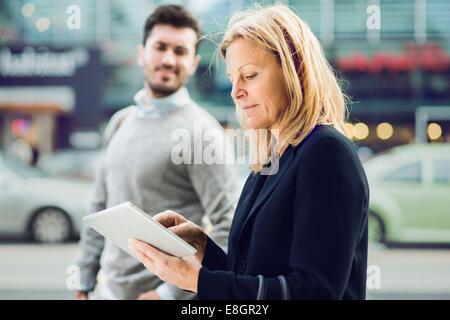 Seitenansicht der Geschäftsfrau mit digital-Tablette auf Stadtstraße mit Kollegen im Hintergrund - Stockfoto