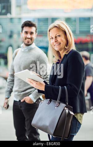 Porträt der Geschäftsfrau mit digital-Tablette auf Stadtstraße mit Kollegen im Hintergrund - Stockfoto