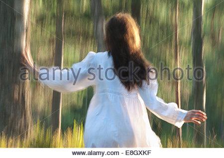 Rückansicht der Frau läuft im Wald - Stockfoto