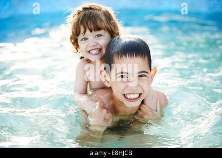 Kinder baden in einem aufblasbaren blaue Schwimmbecken