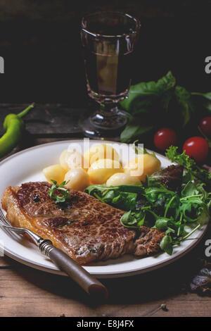 Gegrilltes Steak mit Kartoffeln und grünem Salat auf weißen Keramikplatte und Vintage Glas mit Rotwein über alten - Stockfoto