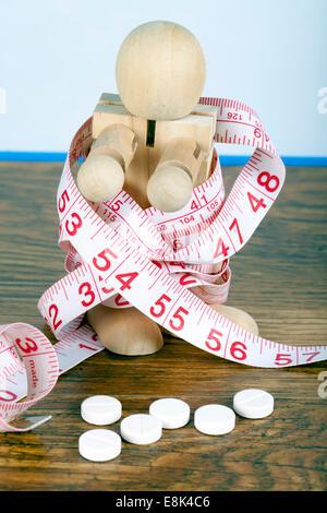 Gewicht-Verlust-Konzept mit hölzernen Mann eingewickelt in Klebeband und Diät-Pillen zu messen - Stockfoto