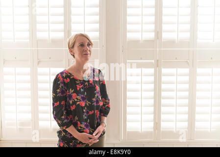 Eine Business-Frau / Mutter mit kurzen Haaren steht durch Jalousien in interessanten Licht - Stockfoto