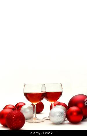 Zwei Gläser Wein gefüllt mit Rotwein sitzen auf einem isolierten weißen Hintergrund in umgeben von Silber und rot - Stockfoto