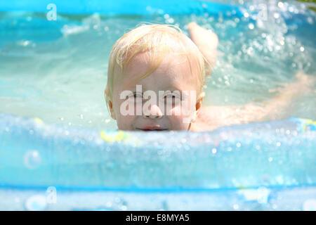 Ein glückliches Baby junge ist über den Rand eines Schwimmbades spähen, als er an einem Sommertag im Wasser spielt. - Stockfoto