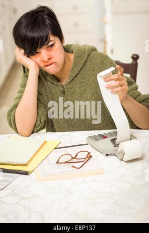 Multi-ethnischen junge Frau qualvollen über finanzielle Berechnungen in ihrer Küche. - Stockfoto
