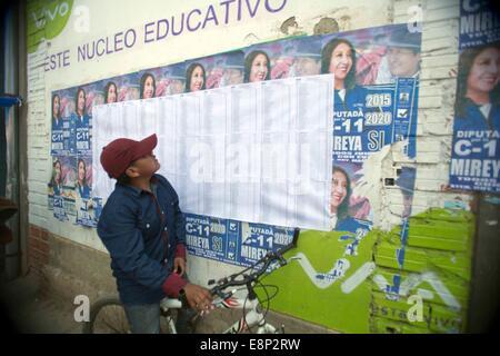 El Alto, Bolivien. 12. Oktober 2014. Ein Junge beobachtet eine Wahlliste an einer Schule in der Stadt El Alto, Bolivien, - Stockfoto