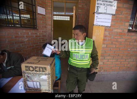 El Alto, Bolivien. 12. Oktober 2014. Ein Polizist wirft seine Stimme an einer Schule in der Stadt El Alto, Bolivien, - Stockfoto