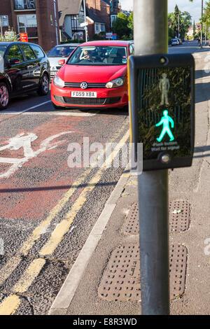 Autos an einem papageitaucher Fußgängerüberweg mit der Steuerung, der Grüne Mann Zeichen beleuchtet, Nottinghamshire, - Stockfoto