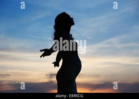 Silhouette der schwangeren Frau fröhlich - Stockfoto