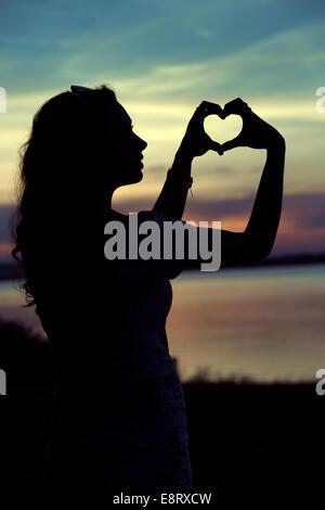 Die Frauen-Silhouette der niedlichen Herzen Geste - Stockfoto