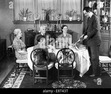 1940ER JAHRE GALADINNER MIT VIER ERWACHSENE UND ZWEI KINDER EIN MANN AM KOPF DES TISCHES SCHNITZEN DER TÜRKEI STEHEN - Stockfoto