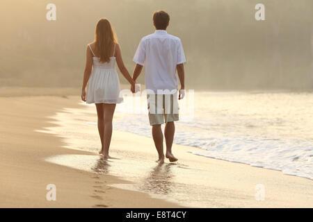 Rückansicht eines Paares zu Fuß und Hand in Hand auf dem Sand des Strandes bei Sonnenuntergang - Stockfoto