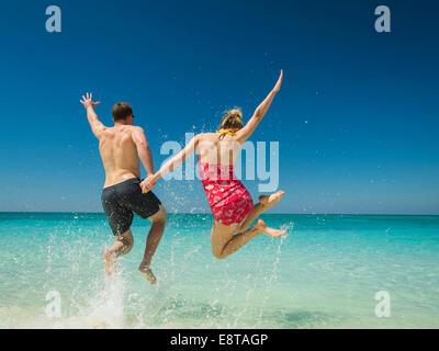 Kaukasische paar springen vor Freude im tropischen Ozean - Stockfoto