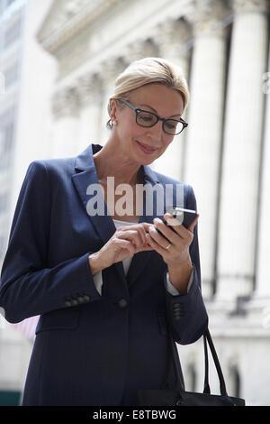 Kaukasische Geschäftsfrau mit Handy in Stadtstraße, New York City, New York, Vereinigte Staaten von Amerika - Stockfoto