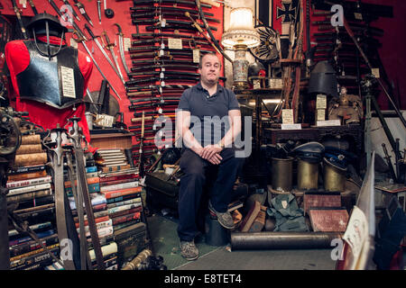 Eine männliche Krämer steht in seiner historischen militärischen Antiquitätengeschäft, umgeben von Waffen, Schwerter, - Stockfoto