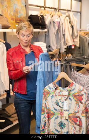 Frau in einer Boutique ist erschrocken über den Preis - Stockfoto
