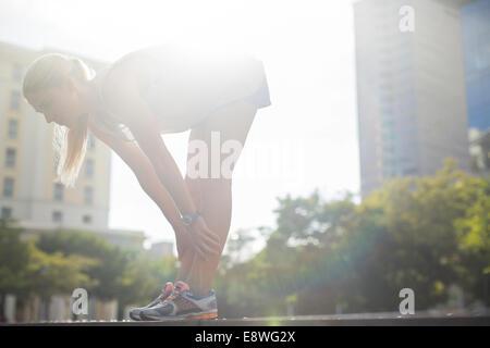 Frau, dehnen vor dem Training auf Stadtstraße - Stockfoto