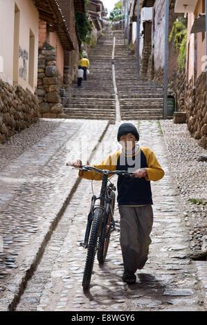 Ein Kind auf dem Fahrrad in einer der die steilen Straßen von dem kleinen Dorf Chinchero im Heiligen Tal in der - Stockfoto
