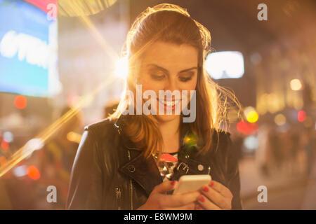 Frau mit Handy auf Stadtstraße in der Nacht - Stockfoto