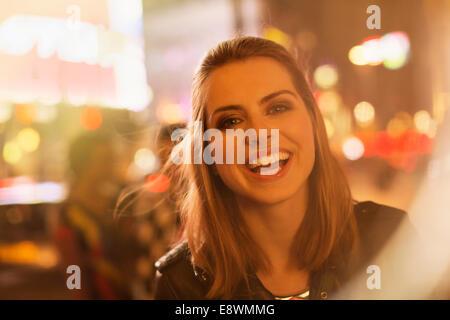Frau lächelnd auf Stadtstraße in der Nacht - Stockfoto
