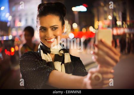 Frau unter Bild mit Handy in der Nacht - Stockfoto