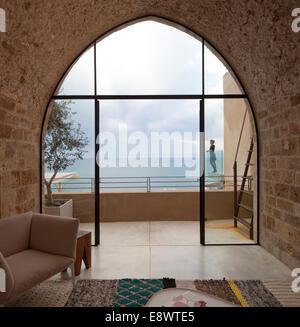 Blick durch gewölbte Fenster Frau stehend auf Balkon mit Blick auf das Meer, Hausbau, T, Israel, Naher Osten. - Stockfoto