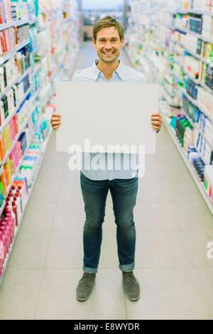 Mann, der leere Karte im Lebensmittelgeschäft Gang hält - Stockfoto